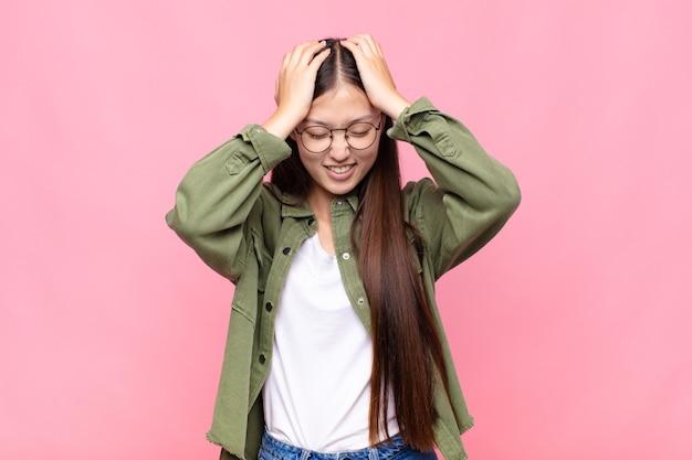 Aziatische jonge vrouw die zich gestrest en gefrustreerd voelt, de handen opheft naar het hoofd, zich moe, ongelukkig en met migraine voelt