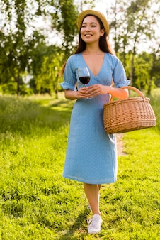 Aziatische jonge vrouw die zich met wijn bij picknick bevindt