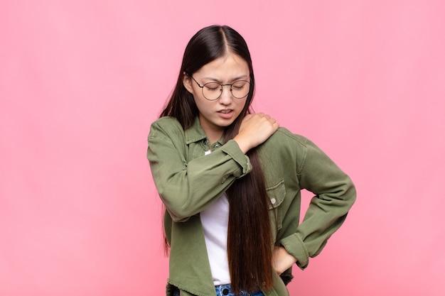 Aziatische jonge vrouw die zich moe, gestrest, angstig, gefrustreerd en depressief voelt, rug- of nekpijn heeft
