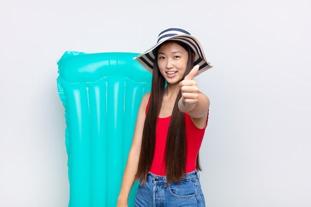 Aziatische jonge vrouw die zich trots, zorgeloos, zelfverzekerd en gelukkig voelt, positief glimlachend met duimen omhoog