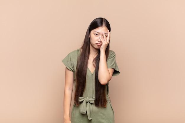 Aziatische jonge vrouw die zich verveeld, gefrustreerd en slaperig voelt na een vermoeiende, saaie en vervelende taak, gezicht met hand vasthoudend