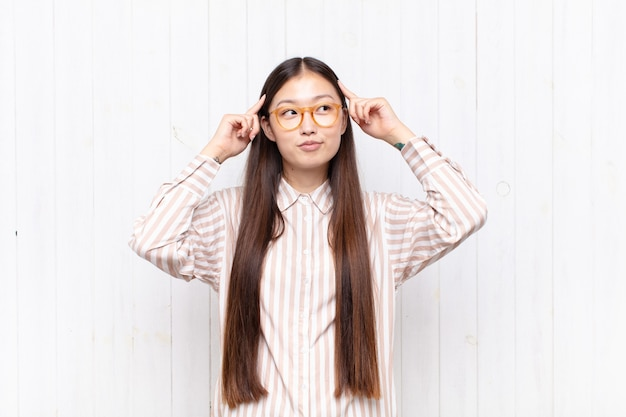 Aziatische jonge vrouw die zich verward voelt of twijfelt, zich concentreert op een idee, hard nadenkt, op zoek is naar ruimte aan de zijkant