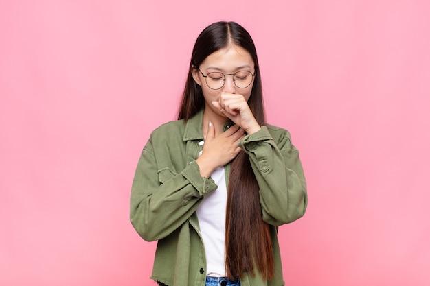 Aziatische jonge vrouw die zich ziek voelt met keelpijn en griepsymptomen, hoesten met bedekte mond
