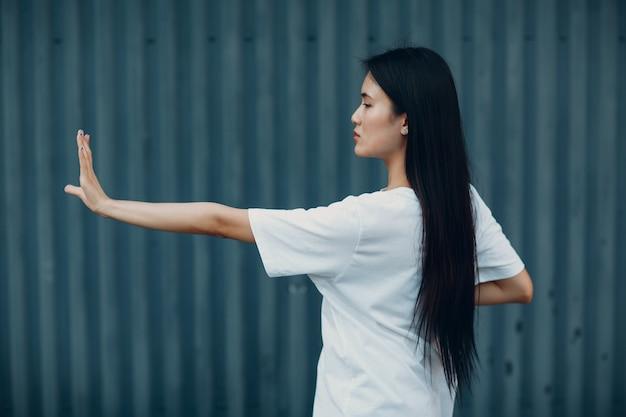 Aziatische jonge vrouw doet qigong oefening zomer buiten. hand vooruit selectieve focus