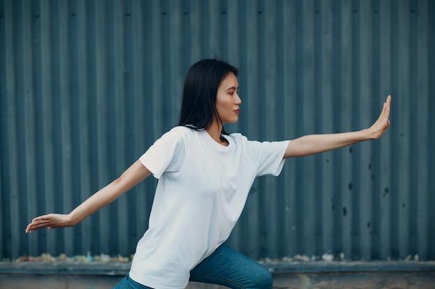 Aziatische jonge vrouw doet qigong oefening zomer buiten.