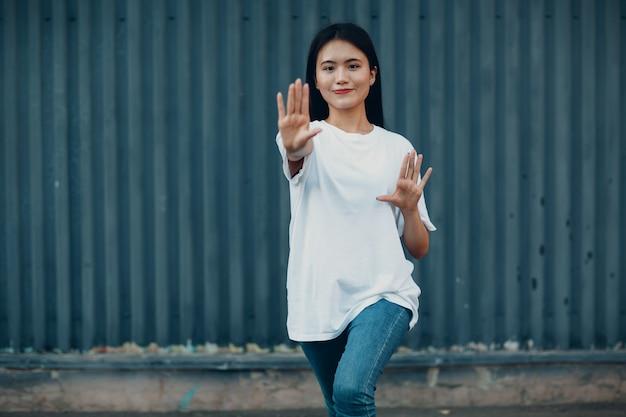 Aziatische jonge vrouw doet qigong oefening zomer buiten