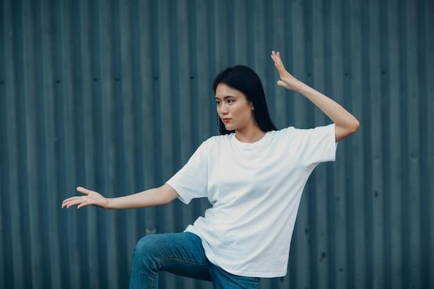 Aziatische jonge vrouw doet qigong of wushu oefening zomer buiten.