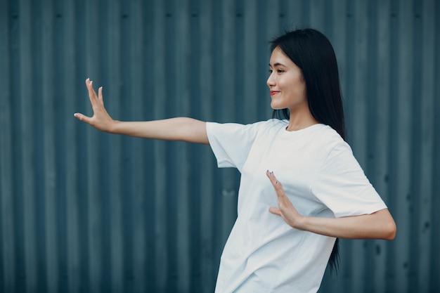 Aziatische jonge vrouw doet qigong taijiquan oefening zomer buiten