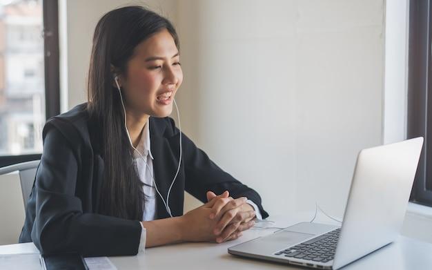 Aziatische jonge vrouw draagt oortelefoons die in videoconferentie spreken