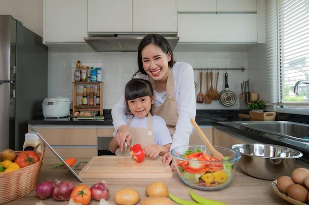Aziatische jonge vrouw en haar dochter kokende salade voor lunch.