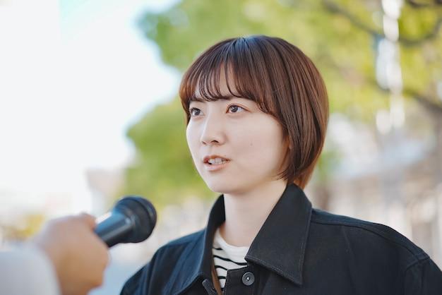 Aziatische jonge vrouw geïnterviewd op straat in de stad