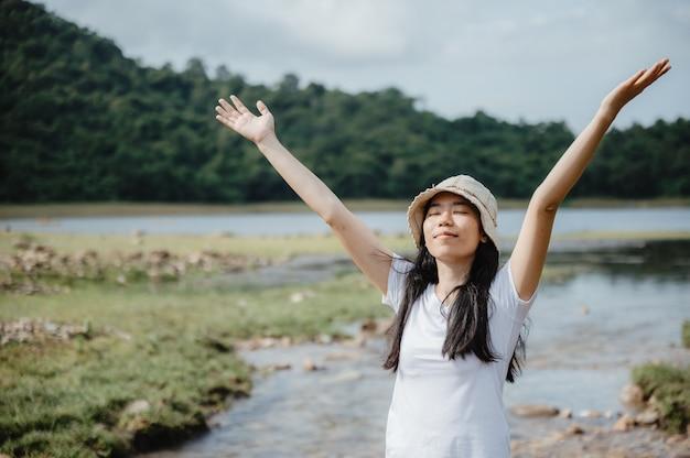 Aziatische jonge vrouw genieten van en ontspannen met de natuur, gebied van waterstroom, waterval buiten