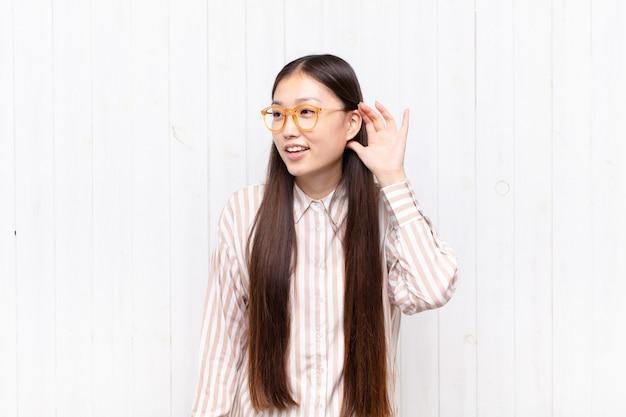 Aziatische jonge vrouw glimlacht, kijkt nieuwsgierig opzij, probeert te luisteren naar roddels of een geheim af te luisteren