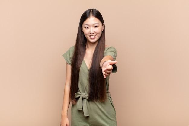 Aziatische jonge vrouw glimlacht, ziet er gelukkig, zelfverzekerd en vriendelijk uit, biedt een handdruk om een deal te sluiten, samen te werken
