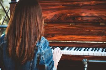 Aziatische jonge vrouw het spelen piano
