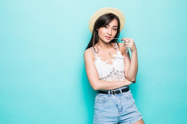 Aziatische jonge vrouw in de zomer clithes en strohoed die op groene muur wordt geïsoleerd