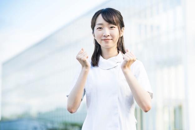 Aziatische jonge vrouw in een witte jas die het lef doet stelt