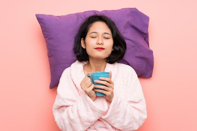 Aziatische jonge vrouw in pyjama's die een kop van koffie houden