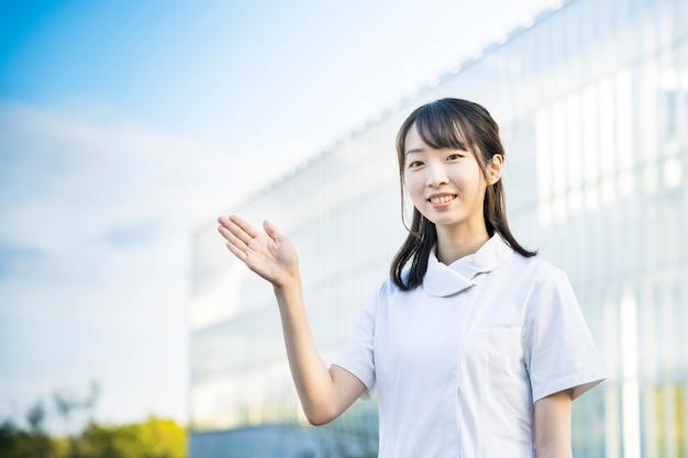 Aziatische jonge vrouw in verpleegsterskleren en poseren met handen
