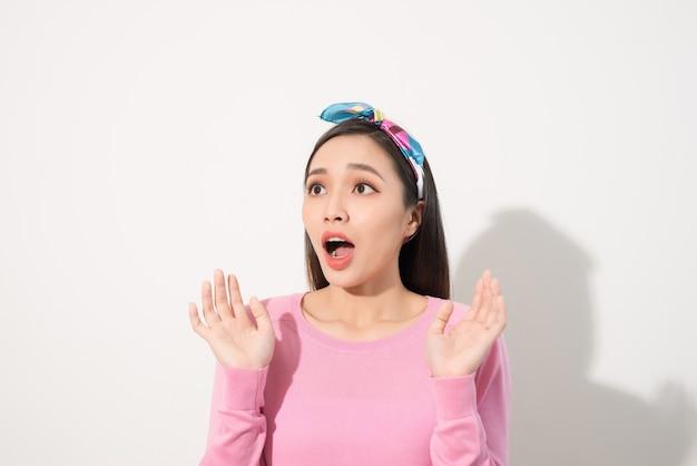 Aziatische jonge vrouw in verrassende emotie, gezicht kijk omhoog met geopende mond en handen, emotioneel van vrouwelijk concept, vooraanzicht