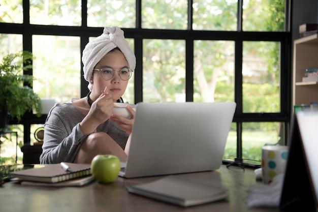 Aziatische jonge vrouw in vrijetijdskleding gebruikend laptop en glimlachend terwijl het werken van huis