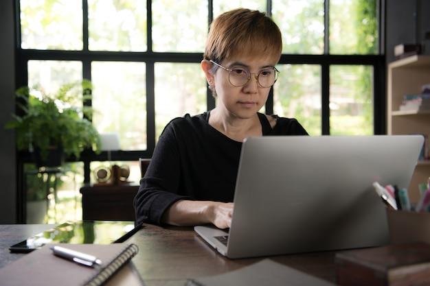 Aziatische jonge vrouw in vrijetijdskleding gebruikend laptop en glimlachend terwijl thuis het werken