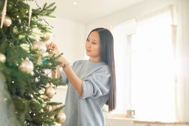 Aziatische jonge vrouw kerstballen opknoping op kerstboom en vakantie voorbereiden