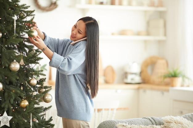 Aziatische jonge vrouw kerstboom versieren tijdens het gesprek op de mobiele telefoon in de woonkamer