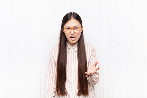 Aziatische jonge vrouw kijkt boos, geïrriteerd en gefrustreerd schreeuwend wtf of wat is er mis met je