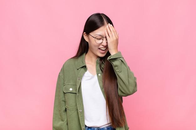 Aziatische jonge vrouw lacht en slapping voorhoofd