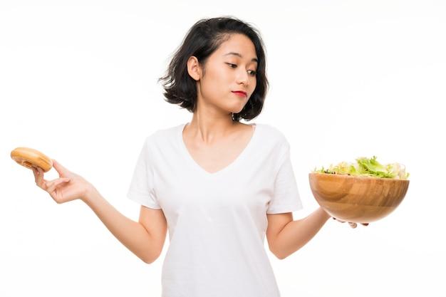 Aziatische jonge vrouw meer dan geïsoleerd met salade en doughnut