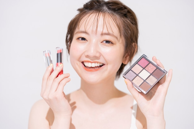Aziatische jonge vrouw met cosmetische artikelen en witte achtergrond