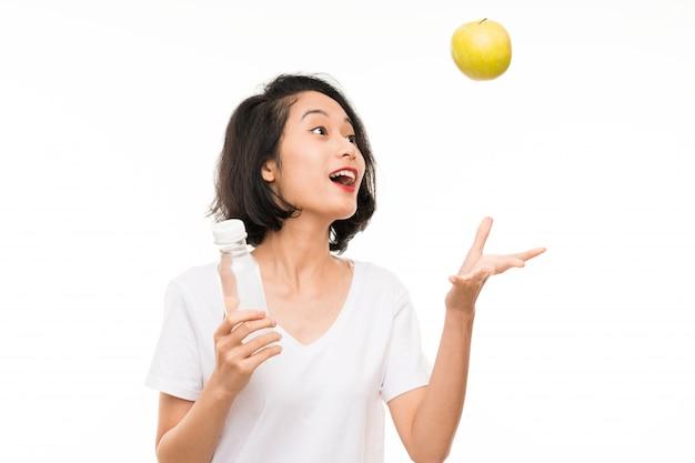 Aziatische jonge vrouw met een appel en een fles water