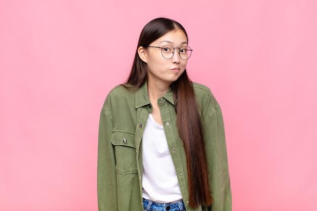 Aziatische jonge vrouw met een gekke, gekke, verbaasde uitdrukking, puffende wangen, zich gevuld, dik en vol eten