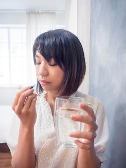 Aziatische jonge vrouw met een glas water en pillen.
