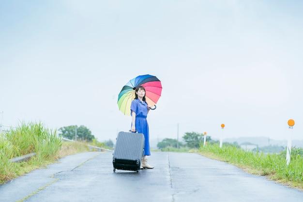 Aziatische jonge vrouw met koffer en kleurrijke paraplu Premium Foto