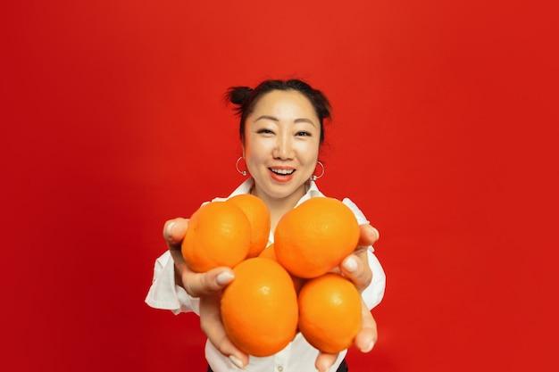 Aziatische jonge vrouw met mandarijnen op rode muur