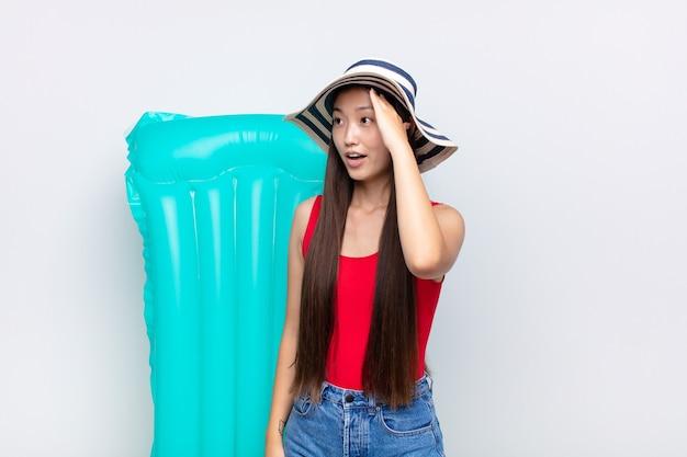 Aziatische jonge vrouw met open mond, geschokt en geschokt op zoek vanwege een vreselijke fout