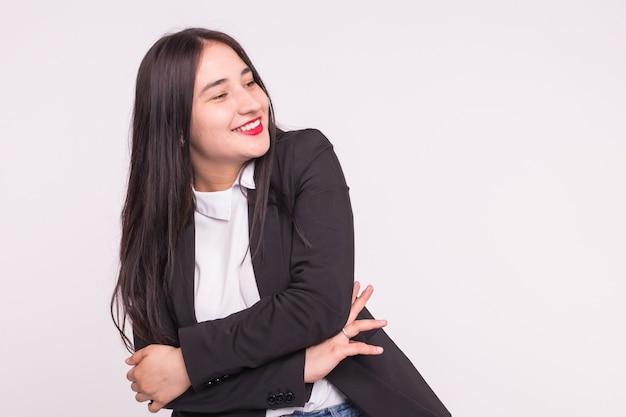 Aziatische jonge vrouw met rode lippen die zwart kostuum in witte muur met exemplaarruimte dragen.