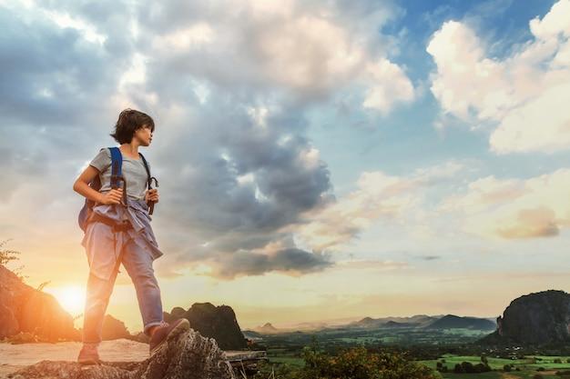 Aziatische jonge vrouw met rugzak die zich op hoogste berg bevindt die met zonsondergang kijkt