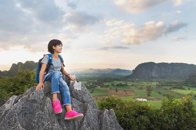 Aziatische jonge vrouw met rugzak zittend op rots van berg, reizen levensstijl concept