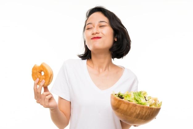 Aziatische jonge vrouw met salade en doughnut