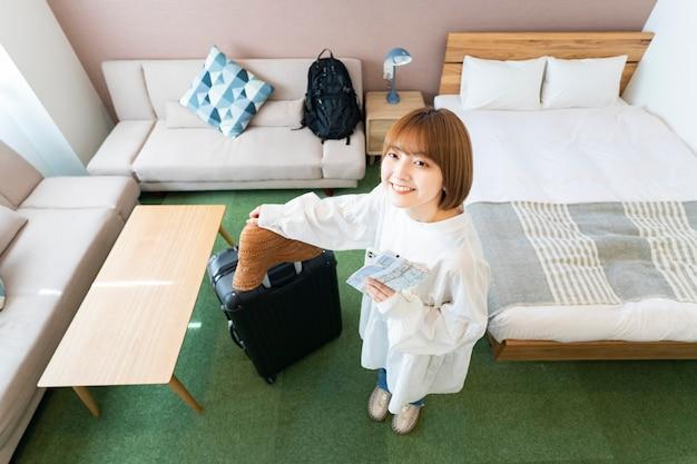 Aziatische jonge vrouw met uitzicht op de hotelkamer