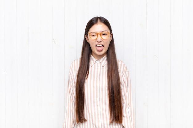 Aziatische jonge vrouw met vrolijke, zorgeloze, rebelse houding, grappen maken en tong uitsteken, plezier maken