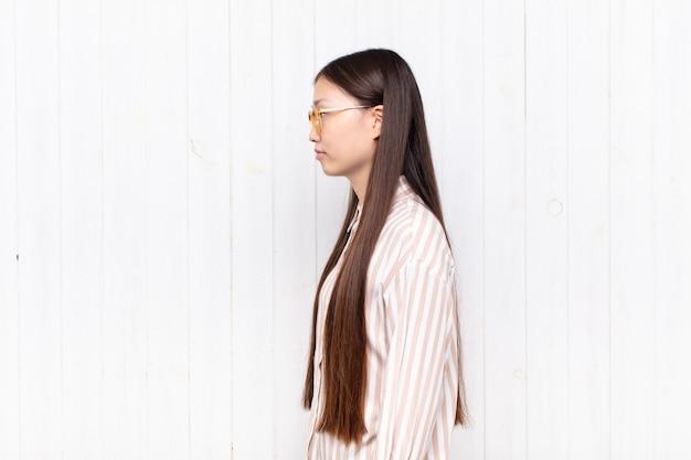 Aziatische jonge vrouw op profielweergave die ruimte vooruit wil kopiëren, denken, zich voorstellen of dagdromen