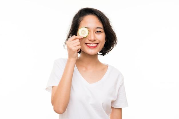 Aziatische jonge vrouw over de geïsoleerde plakken van de muurholding van komkommer
