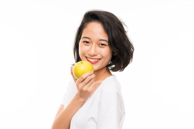 Aziatische jonge vrouw over geïsoleerd met een appel