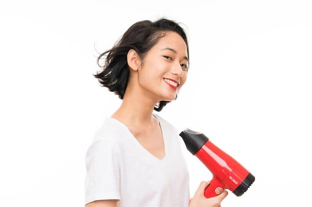 Aziatische jonge vrouw over geïsoleerd met haardroger