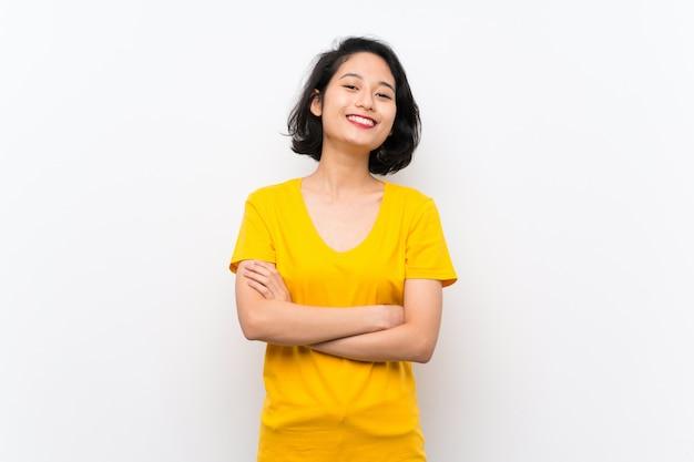 Aziatische jonge vrouw over geïsoleerd wit die de wapens in frontale positie gekruist houden