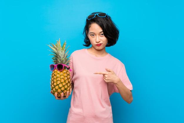 Aziatische jonge vrouw over geïsoleerde blauwe muur die een ananas met zonnebril houdt